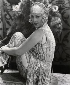 ca. 1920's --- Anita Garvin models pearl beaded outfit in front of large feather fan. Undated photograph. --- Image by © Bettmann/CORBIS