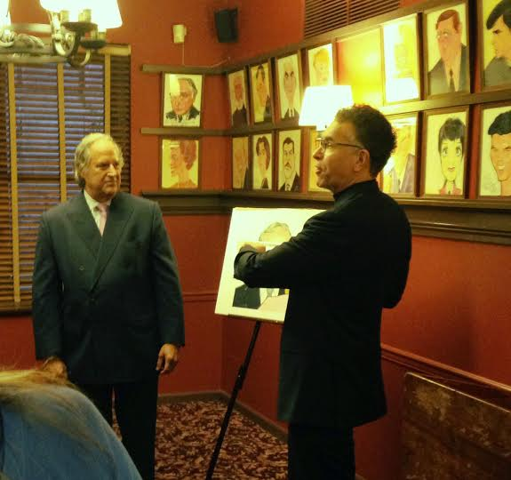 Broadway star and Actor's Fund Chairman Brian Stokes Mitchell presents the caricature to Stewart Lane